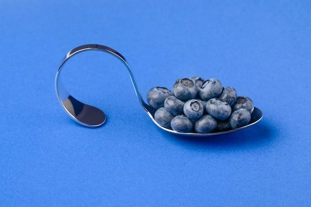 Zakrzywiona chromowana łyżka z jagodami na niebieskim tle