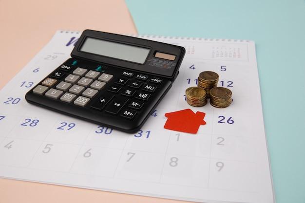 Zakup nowego domu, przypomnienie o harmonogramie spłaty kredytu hipotecznego lub dzień spłaty nieruchomości, czerwony dom z kalkulatorem na białym czystym kalendarzu.