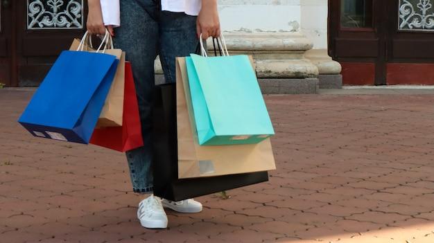 Zakupoholiczka kobieta z papierowymi torbami na zakupy w dłoniach. przytnij zdjęcie. konsumpcjonizm, zakupy, koncepcja stylu życia. skopiuj miejsce na twoje logo. koncepcja sezon zakupów i sprzedaży. czarny piątek czwartek.