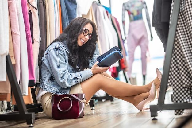 Zakupoholiczka siedzi na podłodze w sklepie z ubraniami zaglądając z wahaniem do swojej torebki z powodu braku pieniędzy.