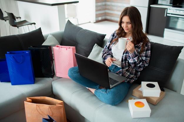 Zakupoholiczka w domu. młoda kobieta korzysta z laptopa i kupuje w internecie wiele towarów w sprzedaży internetowej. zamawia dostawę różnych rzeczy do domu.