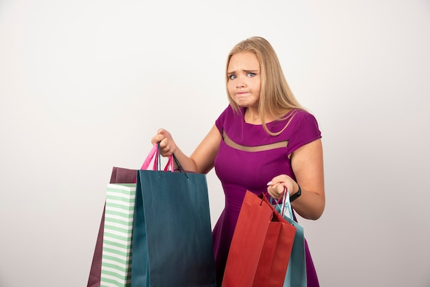 Zakupoholiczka z zakłopotaniem trzymająca kolorowe torby na zakupy.