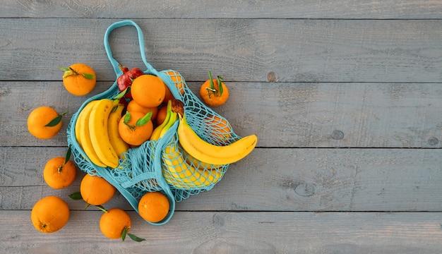 Zakupy artykułów spożywczych bez plastikowych toreb. koncepcja zero waste. ekologiczna, naturalna torba wielokrotnego użytku z organicznymi owocami pomarańczy i bananów. widok z góry z miejscem na kopię, stół z drewna