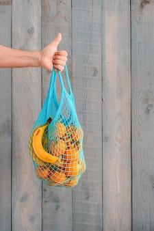 Zakupy artykułów spożywczych bez plastikowych toreb. koncepcja zero waste. męska ręka trzyma ekologiczną torbę wielokrotnego użytku z ekologicznymi owocami, pomarańczami i bananami. skopiuj miejsce, ściana z drewna