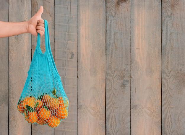 Zakupy artykułów spożywczych bez plastikowych toreb. koncepcja zero waste. męska ręka trzyma ekologiczną torbę wielokrotnego użytku z organicznymi owocami. skopiuj miejsce, tło drewna