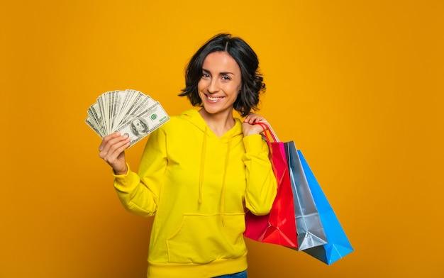 Zakupy były świetne! dziewczyna sukcesu w żółtej bluzie z kapturem, która szeroko uśmiecha się do kamery, pokazując w jednej ręce pieniądze, w drugiej zakupy.