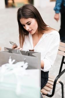 Zakupy dziewczyna patrzeje jej telefon komórkowego