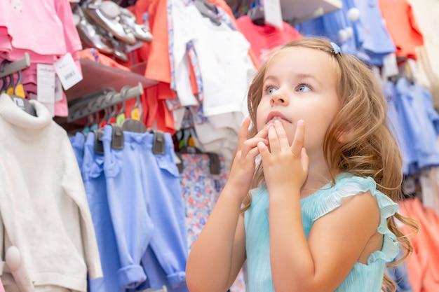 Zakupy. dziewczyna zachwycona pięknymi sukienkami z witryny sklepu.