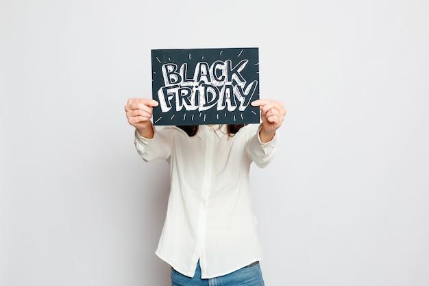 Zakupy, handel detaliczny, czarny piątek, sprzedaż, zakupy i koncepcja ludzie - młoda uśmiechnięta brunetka trzyma znak czarny piątek. wyprzedaż w czarny piątek.