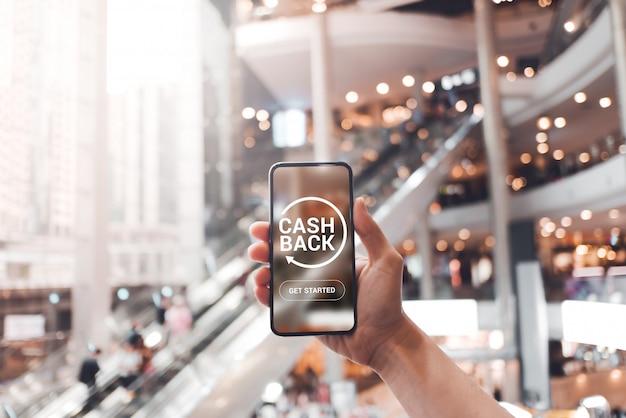Zakupy i cashback pojęcie, zwrot pieniędzy, kobiety ręki mienia smartphone z guzikiem zaczynał cashback przy centrum handlowego tłem.