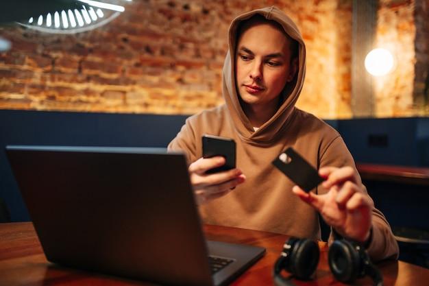 Zakupy i płatność online za pomocą laptopa i karty kredytowej. mężczyzna siedzący w kawiarni, ubrany w zwykły strój, kupuje towary i płaci przez internet, używając czarnej karty debetowej. nowa koncepcja normalności i technologii.