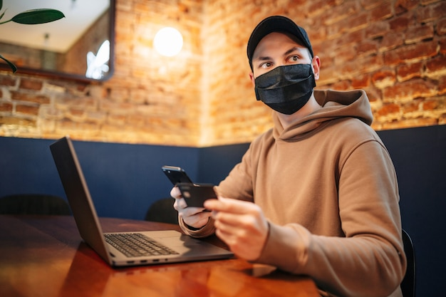 Zakupy i płatność online za pomocą telefonu komórkowego, laptopa i karty kredytowej. mężczyzna w masce podczas pandemii