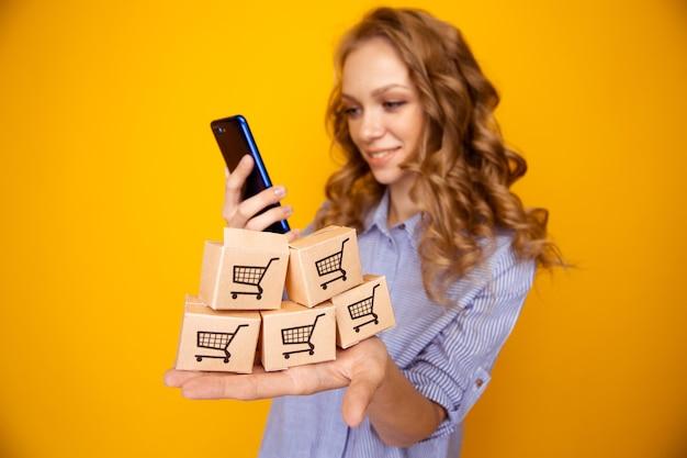 Zakupy internetowe. kobieta trzyma papierowe pudełka i używa telefonu.