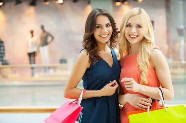Zakupy kobiet. dwie piękne młode kobiety w sukienkach, stojące blisko siebie i trzymające torby na zakupy