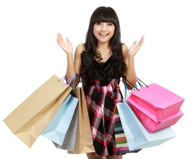 Zakupy kobieta bardzo podekscytowana. zakupy. dynamiczny obraz młodej kobiety na zakupach z dużą ilością toreb.