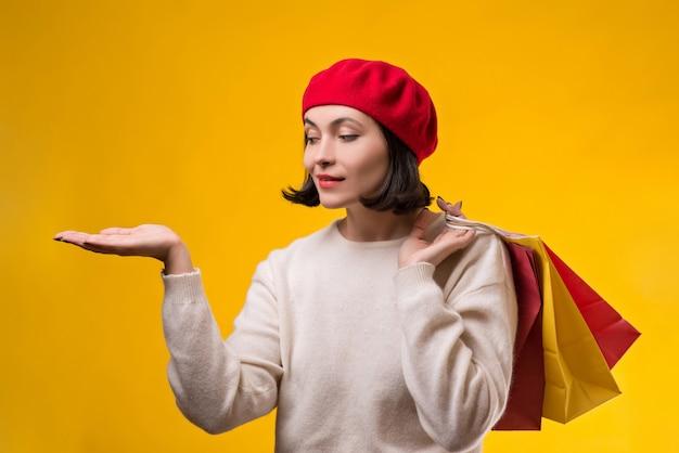 Zakupy kobieta pokazuje coś z otwartej dłoni palmą. torby na zakupy gospodarstwa szczęśliwa kobieta.