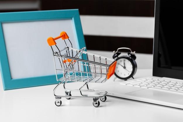 Zakupy koncepcja online. mały zabawkowy wózek i gadżety na stole