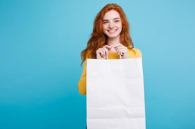 Zakupy koncepcji - zamknij w górę portret młodych piękne atrakcyjne redhair dziewczyna uśmiecha się spojrzenie na aparat fotograficzny z białego torba na zakupy. niebieskie tło pastelowe. skopiuj miejsce.