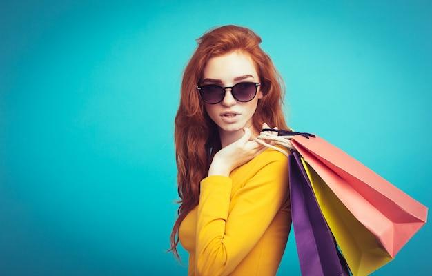 Zakupy koncepcji - zamknij w górę portret młodych piękne atrakcyjne redhair uśmiechnięta dziewczyna spojrzenie na aparat fotograficzny z torby na zakupy. niebieskie tło pastelowe. skopiuj miejsce.