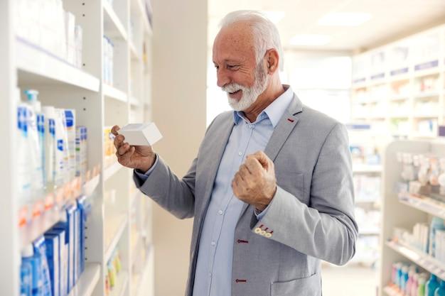 Zakupy leków. starzec w dobrej kondycji fizycznej i psychicznej czyta oświadczenie o leku. cieszy się, bo znalazł opakowanie, które polecił mu farmaceuta