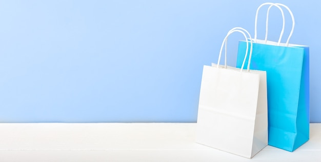 Zakupy makiety torby torby papierowe na biały stół niebieskie tło światła