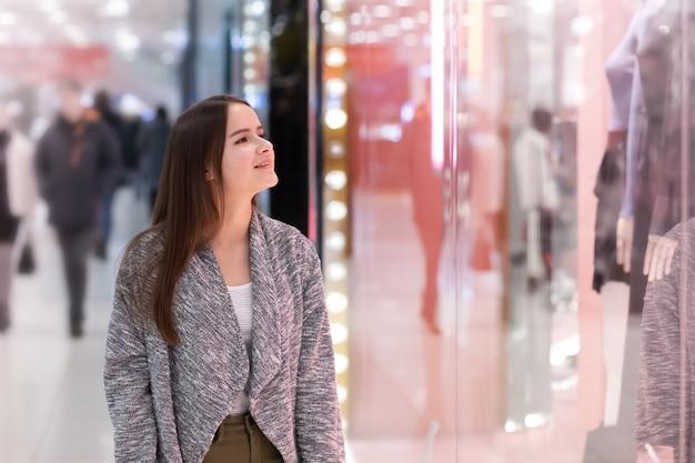 Zakupy młoda dziewczyna patrzy na witryny sklepowe, uśmiecha się, robi zakupy w centrum handlowym.