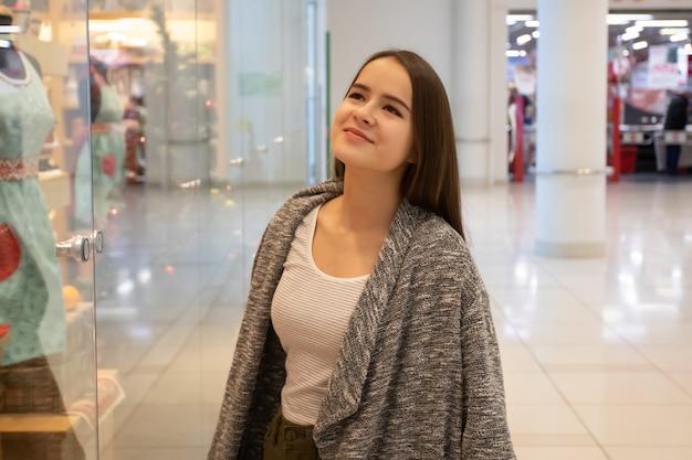 Zakupy młoda dziewczyna patrzy na witryny sklepowe, wybiera prezenty w centrum handlowym.