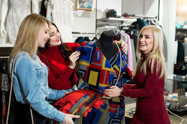 Zakupy, moda i koncepcja przyjaźni - trzech uśmiechniętych przyjaciół przymierzających ubrania w centrum handlowym.