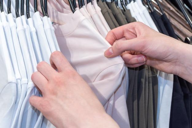 Zakupy, moda, styl – kobiece ręce wybierają ubrania wiszące na wieszaku w sklepie. pomysł na biznes.