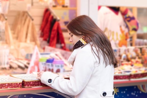 Zakupy noworoczne. młoda dziewczyna wybiera prezenty, pamiątki na jarmarku bożonarodzeniowym