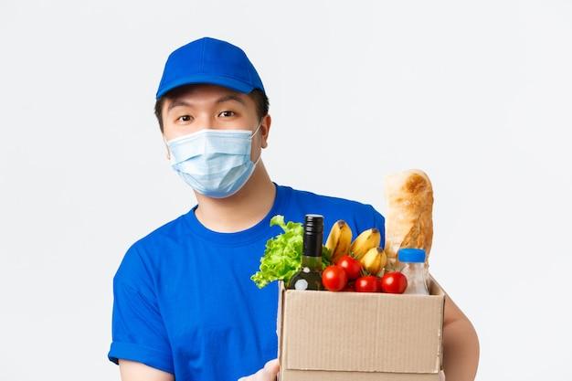 Zakupy online, dostawa jedzenia i koncepcja pandemii covid-19. przystojny uśmiechnięty azjatycki kurier męski w masce medycznej i niebieskim mundurze, przynieś klientowi pudełko z artykułami spożywczymi, wręczając zamówienie