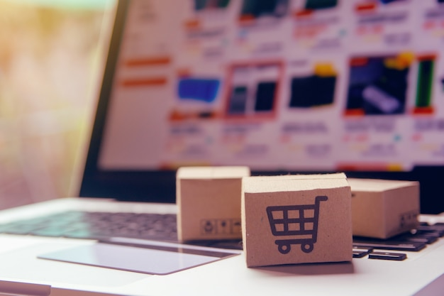 Zakupy online - kartony lub paczki papierowe z logo koszyka i kartą kredytową na klawiaturze laptopa. usługa zakupów w internecie i oferuje dostawę do domu.