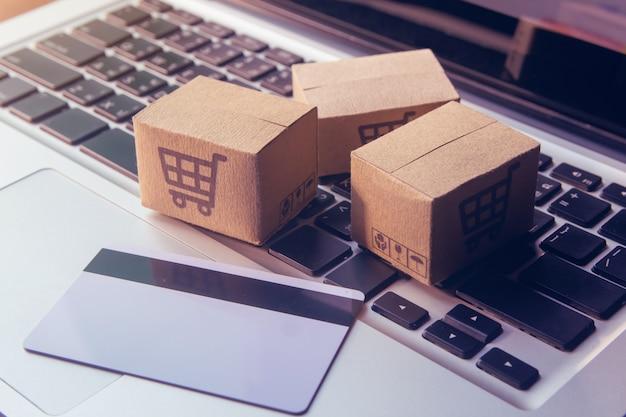 Zakupy online - kartony papierowe lub paczka z logo koszyka i kartą kredytową na klawiaturze laptopa. usługa zakupów w internecie i oferuje dostawę do domu.