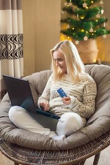 Zakupy online - kobieta płaci za zakupy w sieci kartą kredytową za pomocą laptopa.