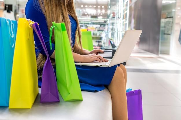 Zakupy online, kobieta w centrum handlowym z laptopem i kartą