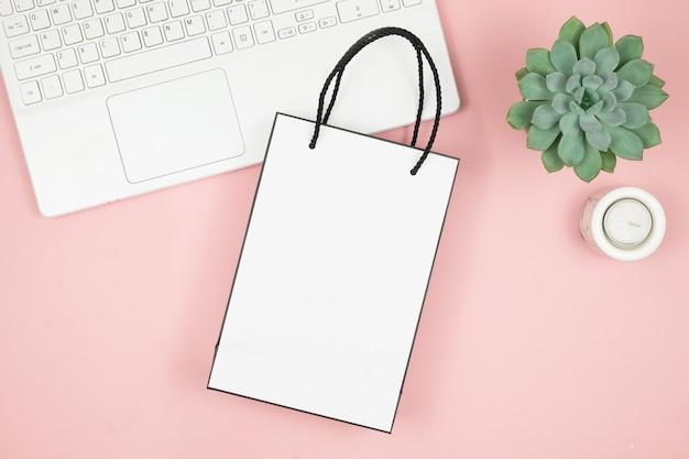 Zakupy online koncepcja. damskie dłonie z telefonem i laptopem na różowej powierzchni. widok z góry, miejsce.