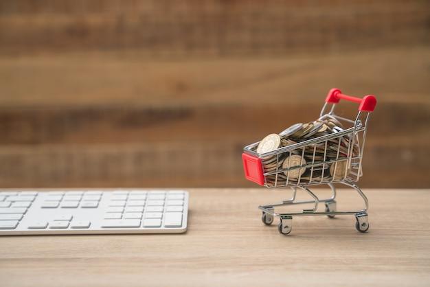Zakupy online koncepcja mały czerwony wózek na stole