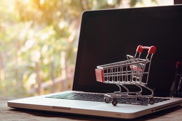 Zakupy online koncepcja. pusty koszyk lub wózek na klawiaturze laptopa. usługa zakupów w internecie. oferuje dostawę do domu.