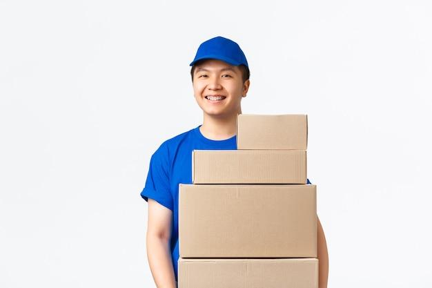 Zakupy online, koncepcja szybkiej wysyłki. przyjemny uśmiechnięty kurier azjatycki, dostawca w niebieskim mundurze przynosi paczki pod drzwi, nosi pudła z zamówieniami i stojące białe tło