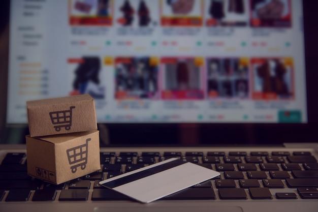 Zakupy online koncepcja - usługi zakupów w internecie. z płatnością kartą kredytową i oferuje dostawę do domu. paczki lub kartony papieru z logo koszyka na klawiaturze laptopa