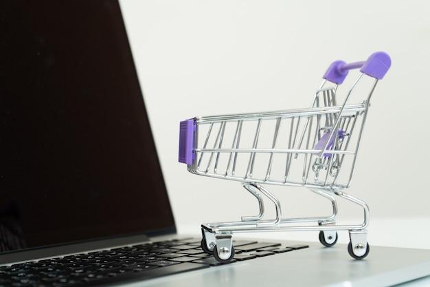 Zakupy online, koszyk na laptopie. koncepcja e-commerce