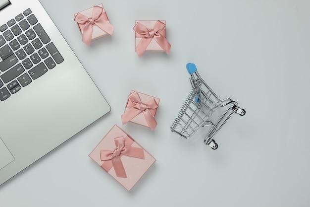 Zakupy online. laptop, wózek na zakupy i pudełka z kokardkami na białym tle. kompozycja na boże narodzenie, urodziny lub wesele. widok z góry