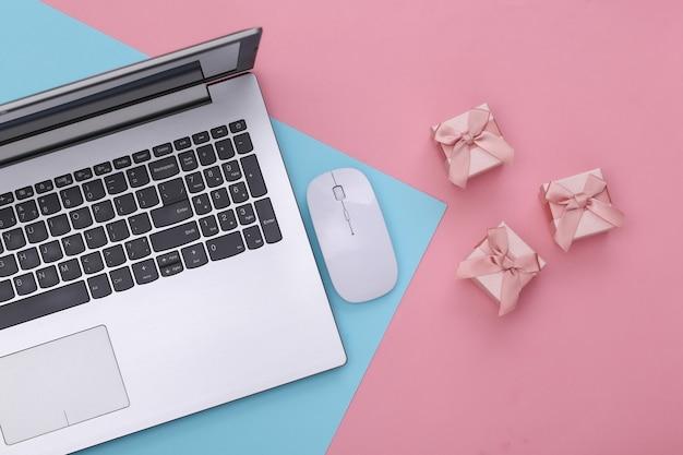 Zakupy online. laptop z myszką pc, pudełka na prezenty na różowym niebieskim tle pastelowych. widok z góry.
