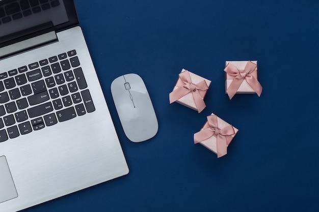 Zakupy online. laptop z myszy komputerowej, pudełka na prezenty na klasycznym niebieskim tle. kolor 2020. widok z góry.