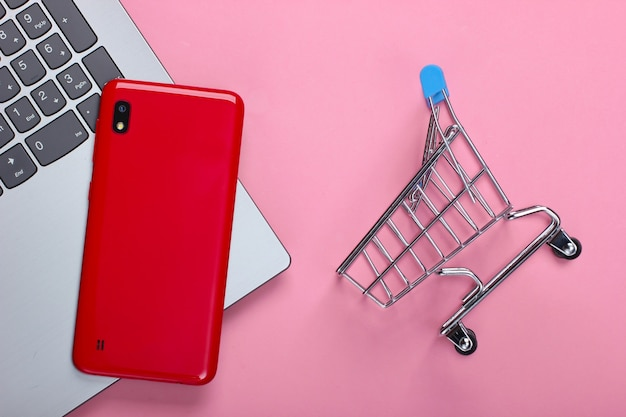 Zakupy online. laptop ze smartfonem i wózkiem na zakupy na różowym pastelu