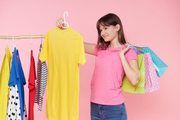 Zakupy online. młoda azjatykcia kobieta z torba na zakupy próbuje dalej kolorową modę odziewa w sklepie. różowe tło