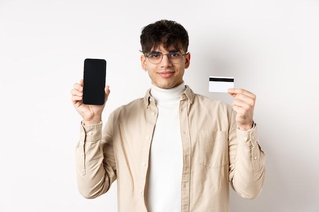 Zakupy online. młody nowoczesny facet pokazuje plastikową kartę kredytową i pusty ekran smartfona, demonstruje konto, stojąc na białej ścianie.