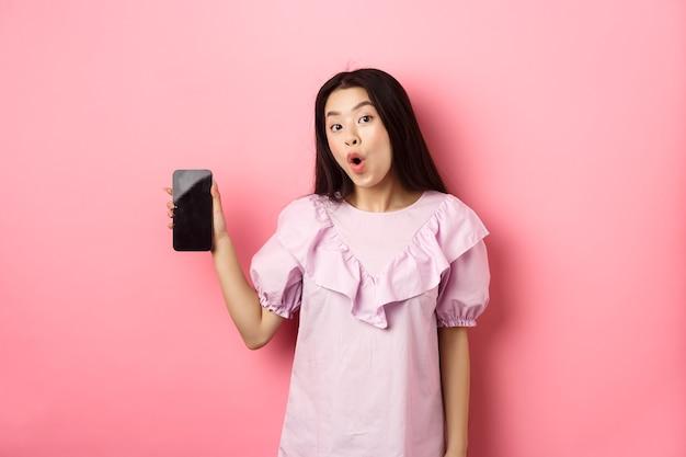 Zakupy online. podekscytowana azjatka mówi wow, pokazując pusty ekran smartfona i patrząc zdziwiona na aparat, stojąc na różowym tle.