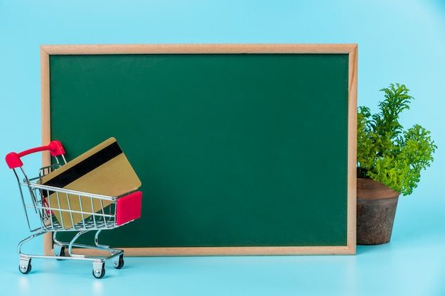 Zakupy online, podwójny wózek umieszczony na zielonej tablicy na niebiesko.