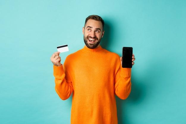 Zakupy online. przemyślany mężczyzna robi zakupy w internecie, pokazując ekran telefonu komórkowego i kartę kredytową, patrząc